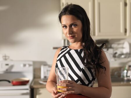 orange juice: pretty woman wearing retro dress and holding glass of orange juice in kitchen Stock Photo