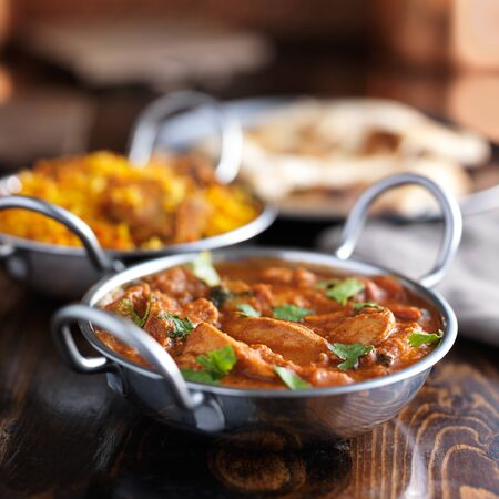 indians: table with indian food and chicken curry in balti dishes