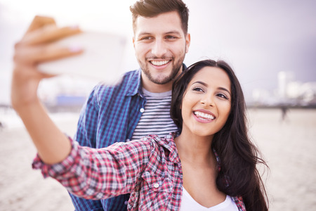 happy couple taking selfie on beach with smartphone