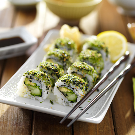 close up food: green themed veggie sushi roll on plate with avocado, kale and cucumber