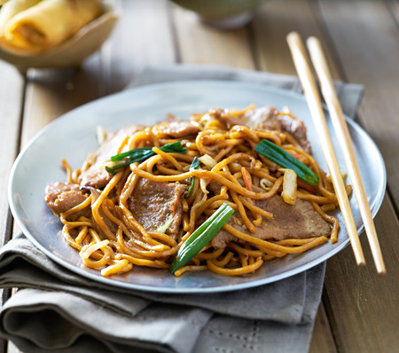 lo mein: chinese food - beef lo mein on a plate with chopsticks Stock Photo