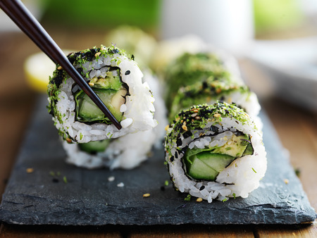 cucumbers: healthy kale and avocado sushi roll with chopsticks