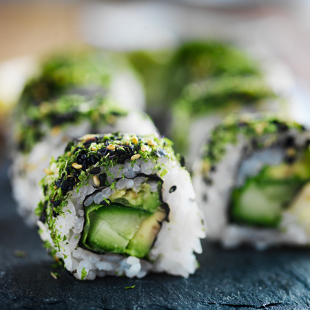 healthy green kale and avocado sushi roll on slate close up