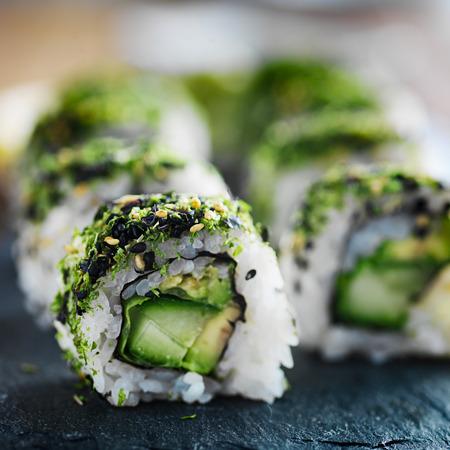 슬레이트 건강한 녹색 양배추와 아보카도 스시 롤을 닫습니다