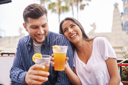 hispanic: romantic hispanic couple drinking beer in outdoor pub