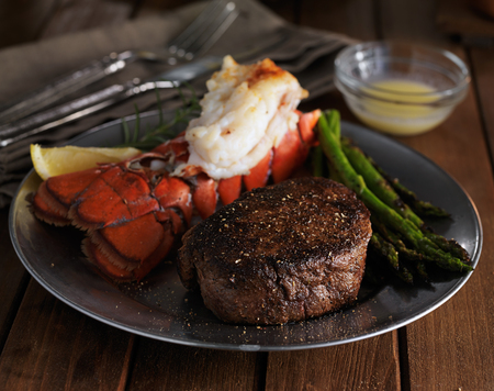 steak and lobster dinner in low key lighting Foto de archivo