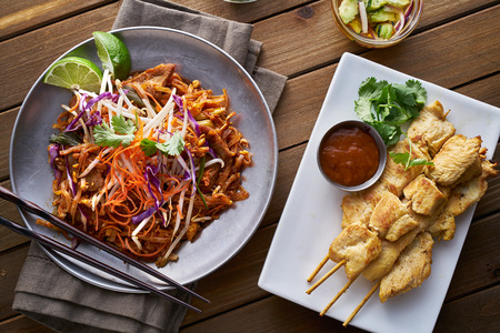 chicken satay: beef pad thai and chicken satay dinner viewed from above