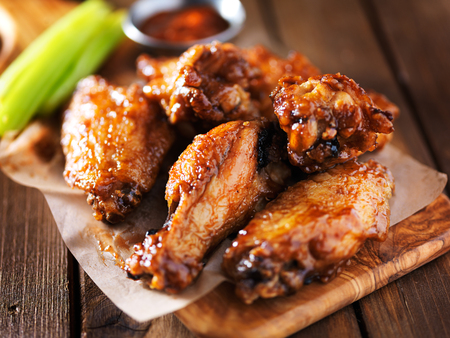 fried: barbecue chicken wings close up on wooden tray Stock Photo