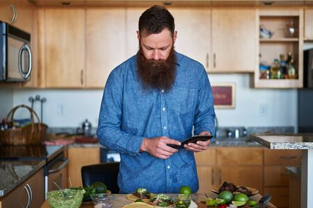 savvy: trendy man with cool beard using tablet or smartphone to look up taco recipe in kitchen