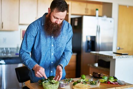 millennial: hipster guy with beard tasting homemade guacamole in kitchen Stock Photo