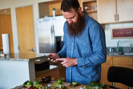 millennial: man making tacos in kitchen and using tablet to look up recipe