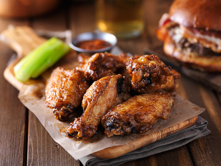 crispy barbecue chicken wings with celery on wooden serving tray