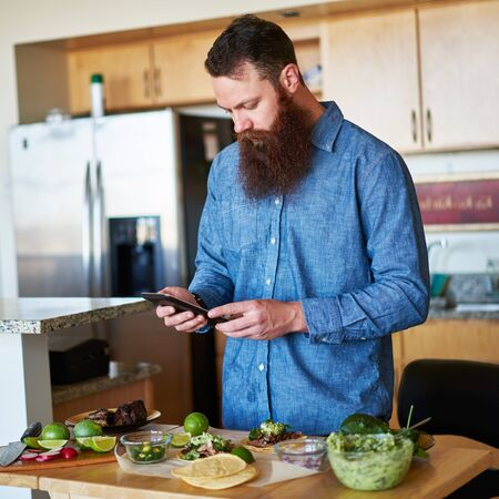prep: bearded man following recipe on tablet to make street tacos Stock Photo