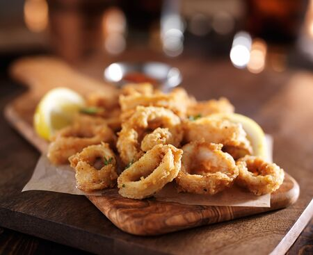 fried calimari rings on wooden tray with dipping sauce