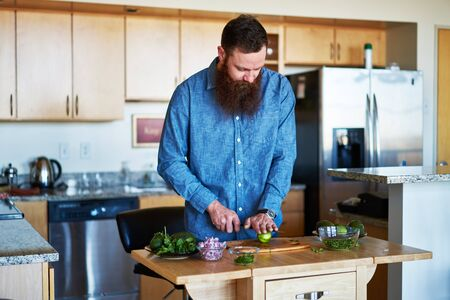 prep: bearded man rolling limes for guacamole recipe in kitchen