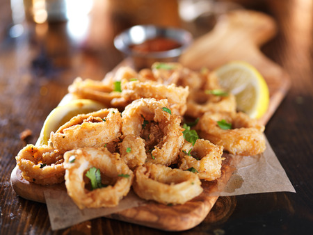 crispy calamari rings on woodne tray with lemon wedge