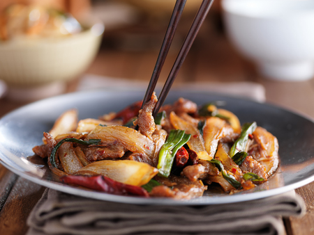 eating a plate of mongolian beef stir fry Stock Photo