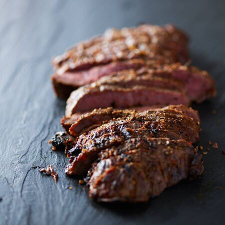 flat iron steak cooked rare and sliced open on slate