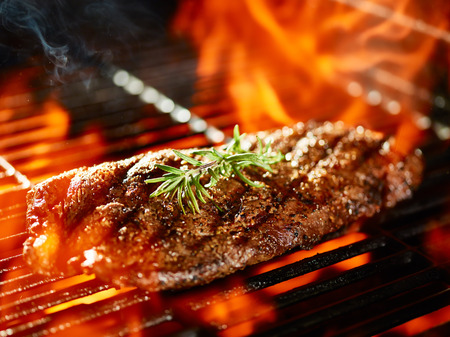 flat iron: flat iron steak cooking on flaming grill with rosemary garnish Stock Photo