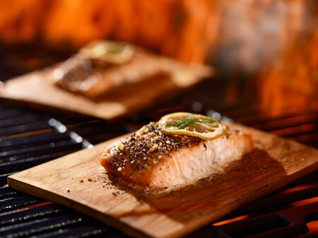 cedar plank salmon with lemon and dill garnish cooking on grill