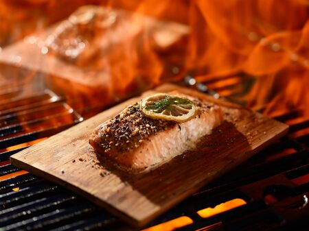 grillng salmon fillets on cedar planks with lemon and dill garnish Stock Photo