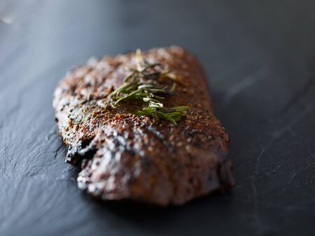grilled flat iron steak resting on slate slab with rosemary garnish Banco de Imagens