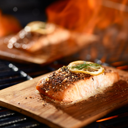 salmon fillets cooking on cedar planks on grill Foto de archivo