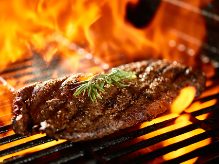 grilling a juicy flat iron steak over open flame Archivio Fotografico