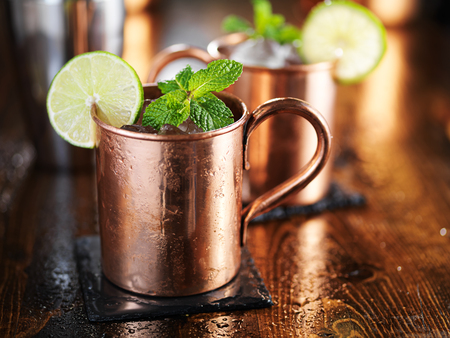 mules: moscow mule cocktail in copper cup with mint and lime garnish