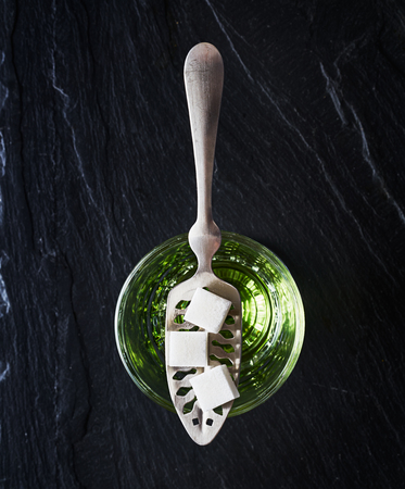 absinthe with sugar cubes and spoon flat lay composition
