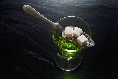 taboo: absinthe in pontarlier glass and spoon with sugar cubes