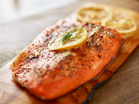 cooked salmon fillet on wooden cedar plank with lemon slices and dill
