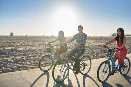 bicycling: happy friend bicycling together on sunny summer beach in california usa
