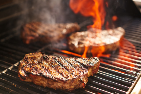 barbequing: steaks cooking over flaming grill Stock Photo