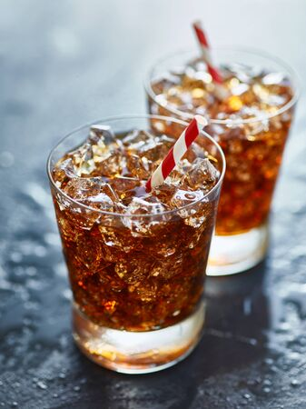 soda pop: two glasses filled with ice and soda pop with striped straw Stock Photo
