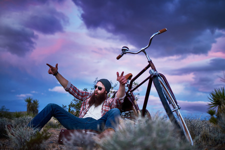 flannel: bearded traveler with suitcase and bike in the desert shouting with arms up Stock Photo