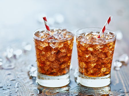 soda pop: side by side glasses of ice cold cola soda pop with retro striped straws