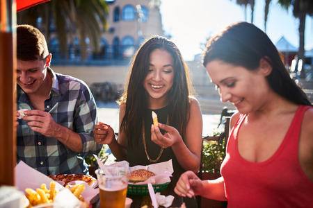 friends eating french fries and hamburgers together at outdoor restaurant under summer sun
