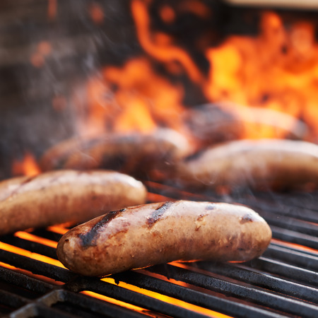 bratwurst sausage barbecue cooking on grill top with flames