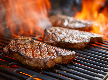 grilling steaks on flaming grill and shot with selective focus Foto de archivo