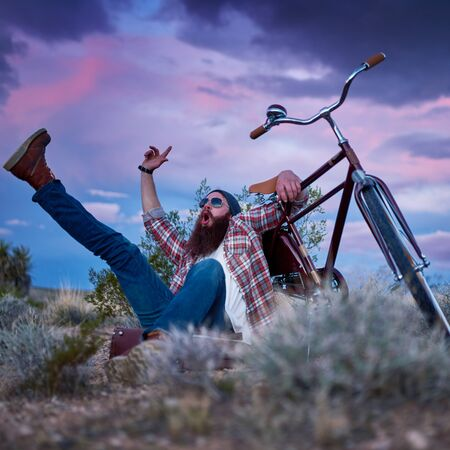suitcases: bearded traveler with arms and foot in the air shouting beside bike in desert