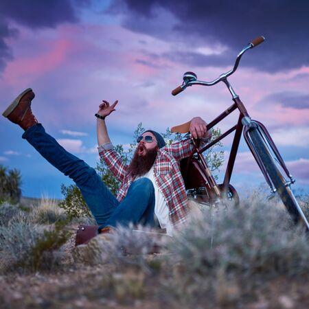 maleta: viajero de barba con los brazos y piernas en el aire gritando lado de la bicicleta en el desierto