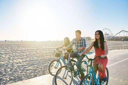 コピー スペースとサンタモニカーのビーチで一緒にバイクに乗って 3 人の友人 写真素材