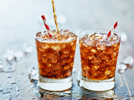 pouring cola into glass with ice and strip straw on table top