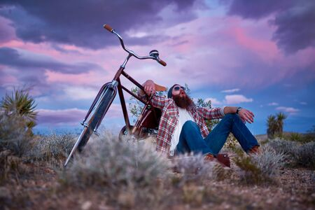 vagabond: bearded man with bike in desert shouting Stock Photo