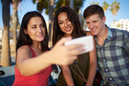 three palm trees: group selfie with three friends sitting in the shade under palm trees in santa monica Stock Photo