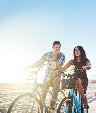 stopped: couple on bicycles stopped at sunny california beach Stock Photo