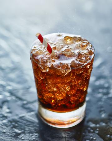 soda pop: fizzy glass of cold cola soda pop with retro stiped straw Stock Photo