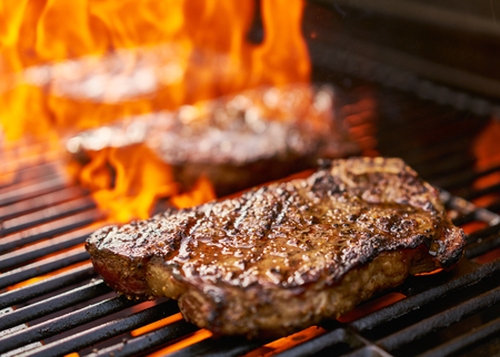 new york strip: grilling new york strip steaks over flames