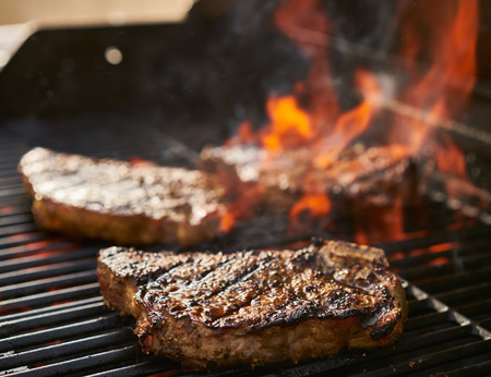 new york strip: bone-in new york strip steaks cooking over flaming grill Stock Photo